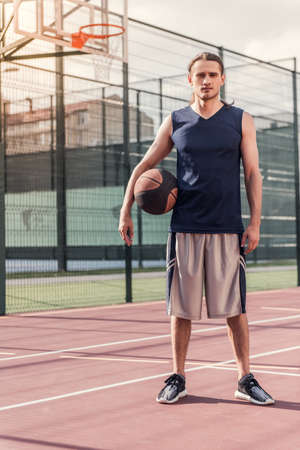 Full length portrait of young basketball player standing with a ball on basketball court outdoors Stock Photo