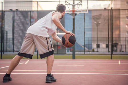 Handsome basketball player is playing on basketball court outdoors Stock Photo