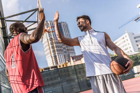 Handsome basketball players are greeting and smiling before the game on basketball court outdoors