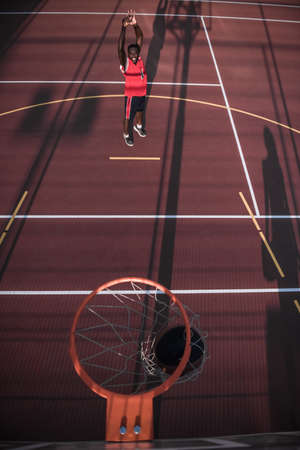 Top view of handsome Afro American basketball player shooting a ball through the hoop while playing on basketball court outdoors Stock Photo