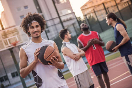 Handsome basketball players are talking and smiling on basketball court outdoors, mulatto guy in the foreground is looking at camera
