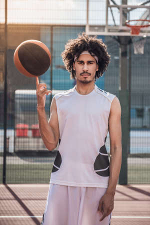 Attractive mulatto basketball player is spinning a ball on his finger and looking at camera while standing on basketball court outdoors Stock Photo