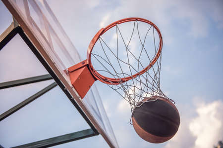 Low angle view of basketball hoop in outdoor court, ball getting through
