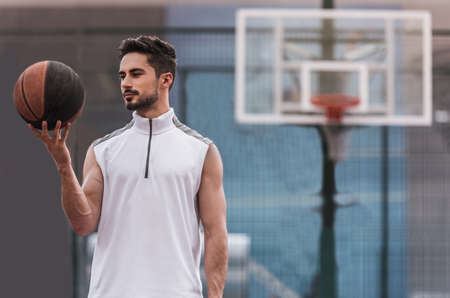 Handsome basketball player is holding a ball while standing on basketball court outdoors