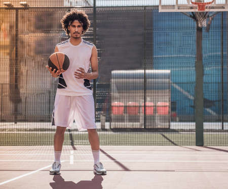 Full length of attractive mulatto basketball player holding a ball while playing on basketball court outdoors
