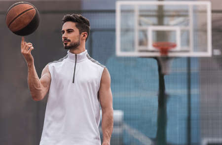Handsome basketball player is spinning a ball on his finger while standing on basketball court outdoors