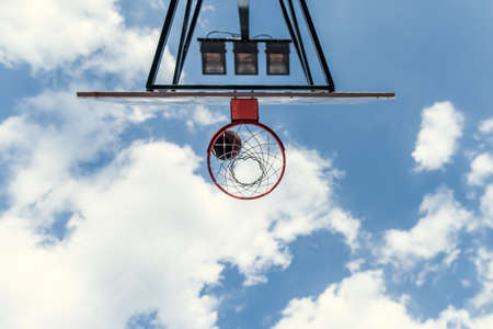 Bottom view of basketball hoop on blue sky background Stock Photo
