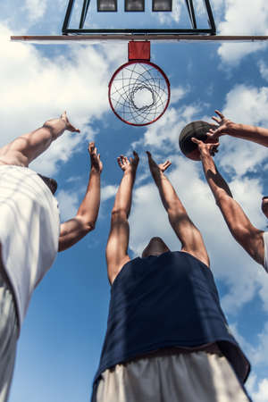 Bottom view of handsome basketball players shooting a ball through the hoop while playing on basketball court outdoors Stock Photo