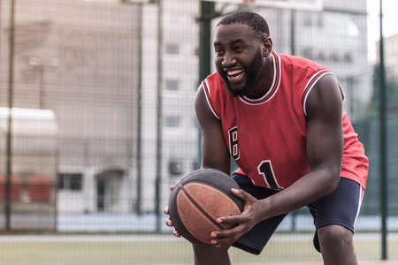 Handsome Afro American basketball player is playing on basketball court outdoors