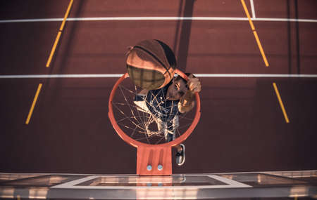 Top view of handsome basketball player shooting a ball through the hoop while playing on basketball court outdoors