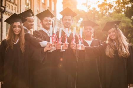 アカデミック ドレスの成功した卒業生の卒業証書を持って、カメラ目線、屋外で立ってながら笑顔