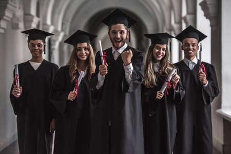 アカデミックドレスの成功した卒業生は、大学のホールに立っている間、カメラと笑顔を見て、卒業証書を保持しています