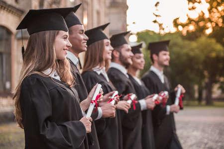 アカデミックドレスの成功した卒業生は、屋外で列に立っている間、楽しみにして卒業証書を保持しています