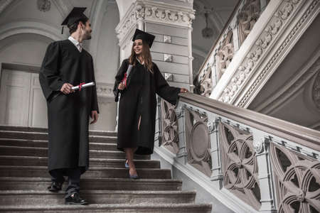Successful couple of graduates in academic dresses are holding diplomas, talking and smiling while going downstairs in university building Stock Photo