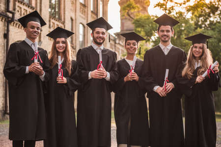 Successful graduates in academic dresses are holding diplomas, looking at camera and smiling while standing outdoors Stock Photo