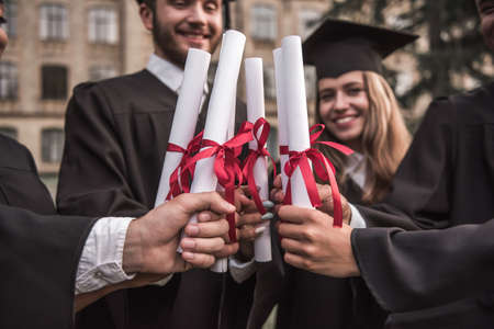 Cropped image of successful graduates in academic dresses holding diplomas and smiling while standing outdoors