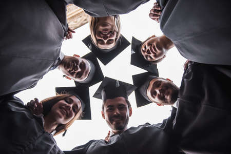 Bottom view of successful graduates in academic dresses looking at camera and smiling while standing outdoors Stock Photo