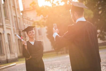 アカデミック ドレスの成功した卒業生が屋外立ちながらお互いの卒業証書と記念撮影します。