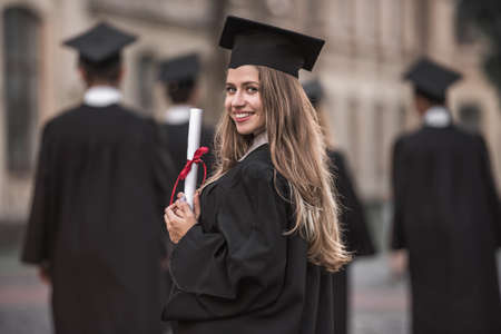 Beautiful female graduate in academic dress is holding diploma, looking at camera and smiling while standing outdoors Reklamní fotografie - 88355260