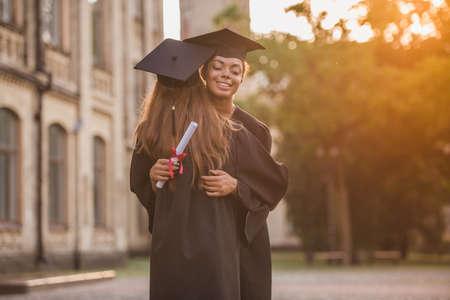 アカデミックドレスの美しい女性卒業生は、屋外で立っている間、抱きしめて微笑んでいます