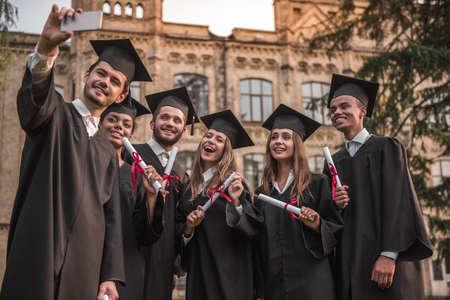 アカデミックドレスの成功した卒業生は、屋外で立っている間、カメラと笑顔を見て、卒業証書を保持している、男はそれらの写真を取っています