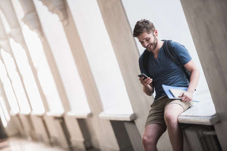 Attractive young student is using a smart phone and smiling while sitting on the window-sill in university hall