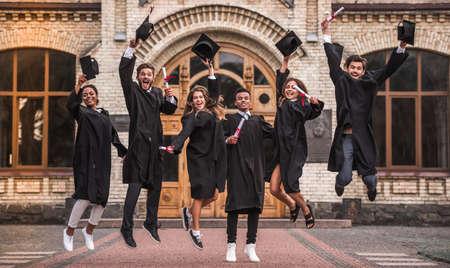 Erfolgreiche Absolventen in akademischen Kleidern halten Diplome ab, betrachten die Kamera und lächeln, während sie draußen nach dem Foto springen