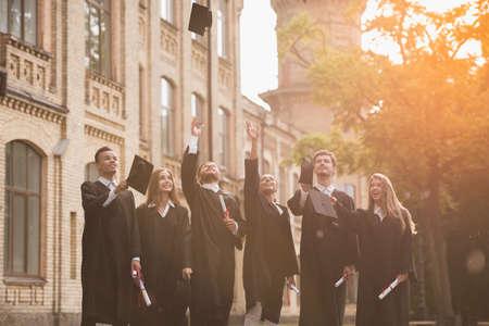 アカデミックドレスで成功した卒業生は、屋外で立っている間、彼らのキャップを投げ、笑顔を、卒業証書を保持している