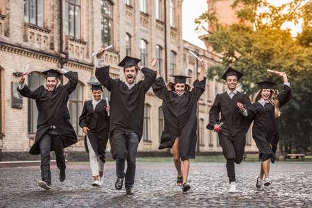Erfolgreiche Absolventen in akademischen Kleidern halten Diplome ab, betrachten die Kamera und lächeln beim Laufen im Freien
