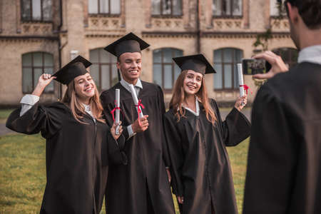 Successful graduates in academic dresses are holding diplomas, looking at camera and smiling while standing outdoors, guy is taking photo of them