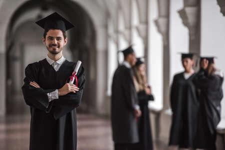 アカデミック ドレスの成功した卒業生は、大学のホールで話している、フォア グラウンドで男は卒業証書を持って、カメラ目線し笑顔