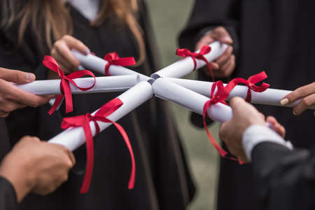 Cropped image of successful graduates in academic dresses holding diplomas while standing outdoors Archivio Fotografico