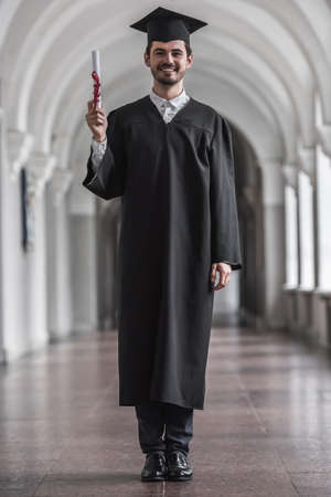 Handsome  young graduate in academic dress is holding diploma, looking at camera and smiling while standing in university hall Stock Photo