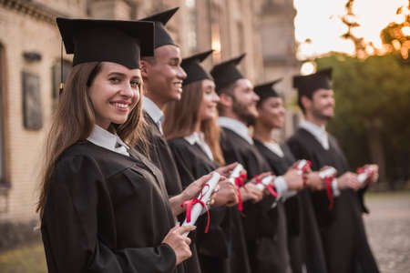 Successful graduates in academic dresses are holding diplomas, looking forward and smiling while standing in a row outdoors