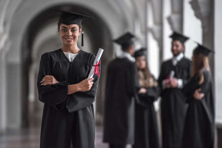 Successful graduates in academic dresses are talking in university hall, girl in the foreground is holding diploma, looking at camera and smiling