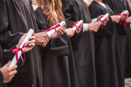 アカデミック ドレスの成功した卒業生の卒業証書を保持、楽しみ、行外に立ちながら笑顔 写真素材