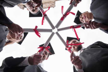 Bottom view of successful graduates in academic dresses holding diplomas and smiling while standing outdoors Stock Photo