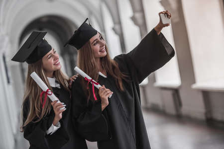 Attractive young female graduates in academic dresses are holding diplomas, doing selfie and smiling while standing in university hall Stock Photo