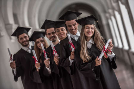 졸업식을 성공적으로 마친 졸업생들은 대학 복도에 서있는 동안 카메라를보고 웃고 졸업장을 받았습니다.