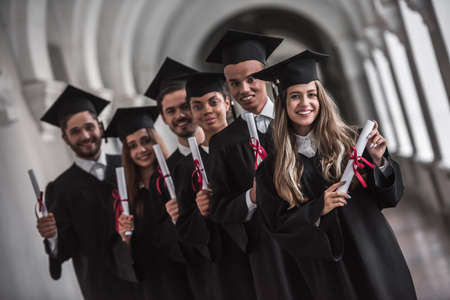 Successful graduates in academic dresses are holding diplomas, looking at camera and smiling while standing in university hall