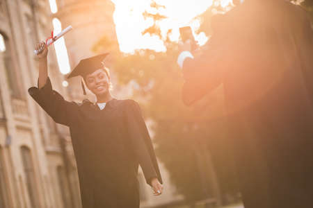 Successful graduates in academic dresses are taking photos with diplomas of each other while standing outdoors