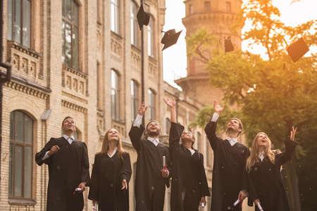 Erfolgreiche Absolventen in akademischen Kleidern halten Diplome ab, werfen ihre Mützen auf und lächeln im Freien