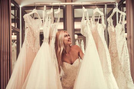 魅力的な若い花嫁は現代のウェディング サロンでウェディング ドレスを選択しながら笑っています。 写真素材