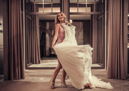 Lovely young bride is smiling while choosing elegant wedding dresses in modern wedding salon