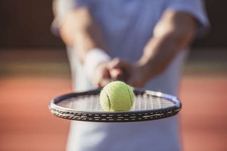 Handsome man is holding tennis racket and ball while standing on tennis court outdoors Stock Photo
