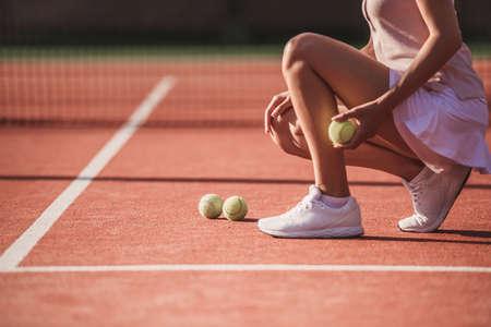 屋外のコートでテニスをしながらテニスボールを持って女の子のトリミングされた画像 写真素材 - 88858588