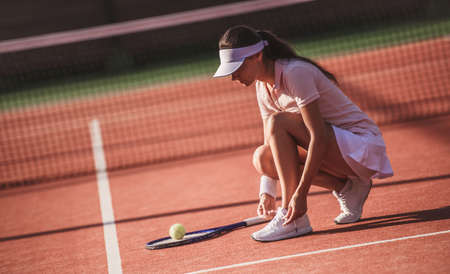 Beautiful young girl is lacing her trainers while playing tennis on court outdoors