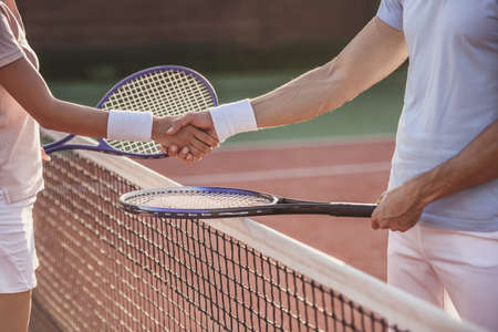 Cropped image of man and woman shaking their hands while playing tennis on tennis court outdoors