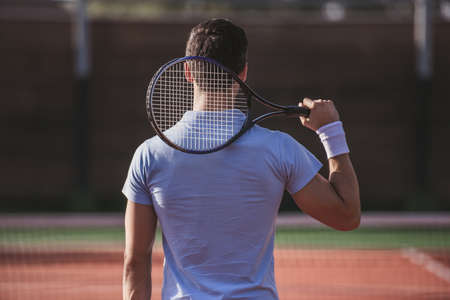 Back view of young man holding tennis racket while playing tennis on court outdoors Stock Photo