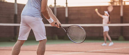 Beautiful young woman and handsome man are playing tennis on tennis court outdoors